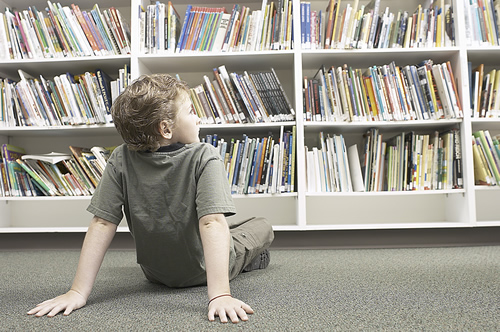 Boy sitting on floor looking at library books on shelf